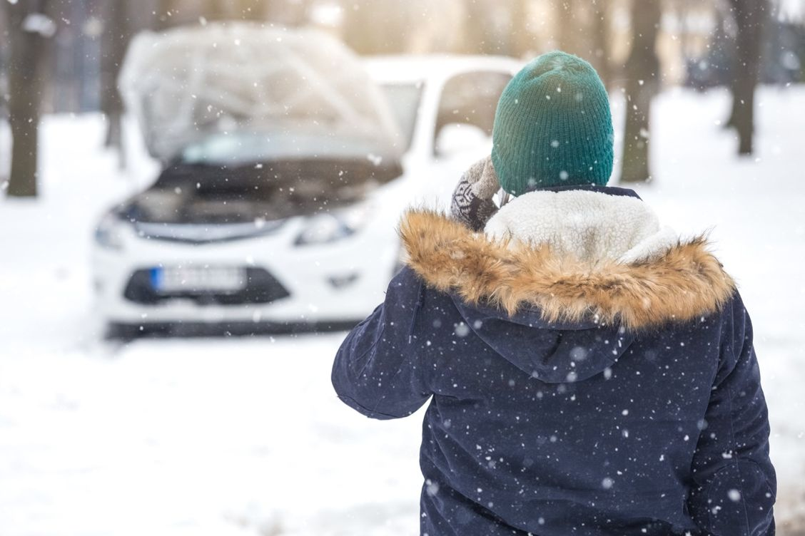 lady standing in winters snow in front of car