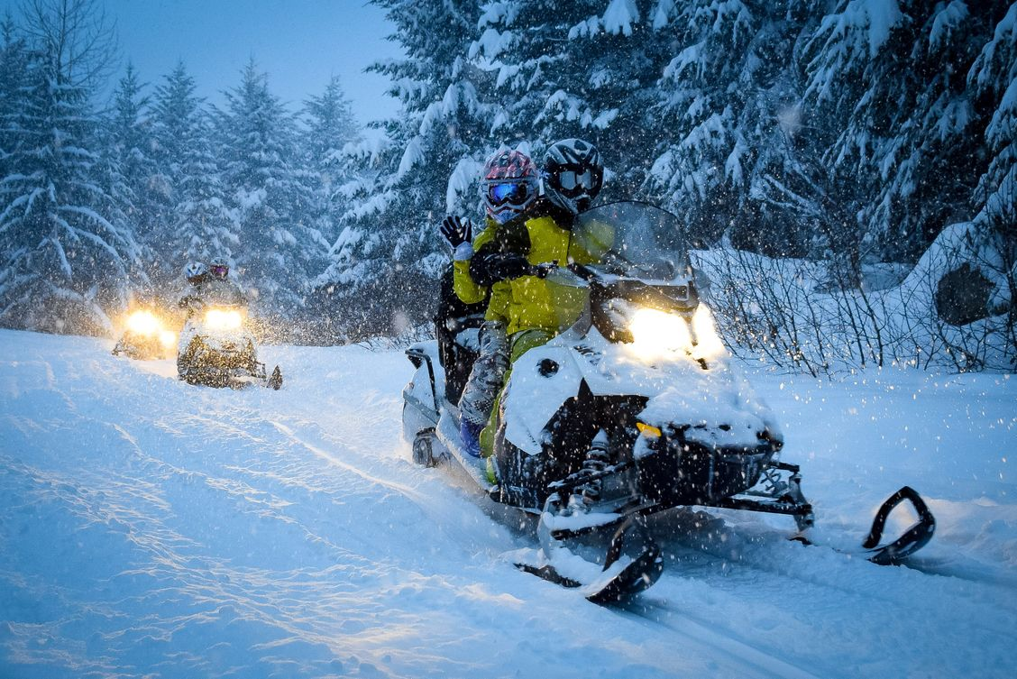fully charged snowmobiles riding through the evening in a forest